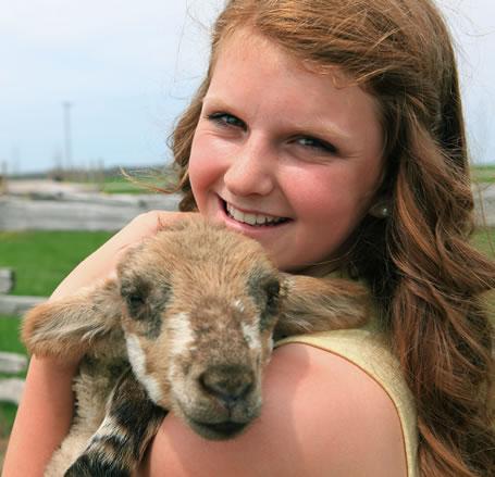 Teenage girl holding a farm animal