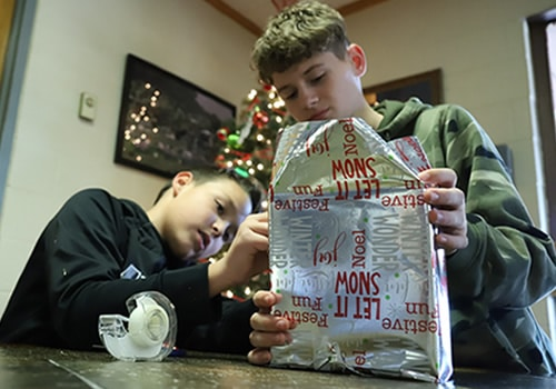 two boys wrapping a Christmas gift