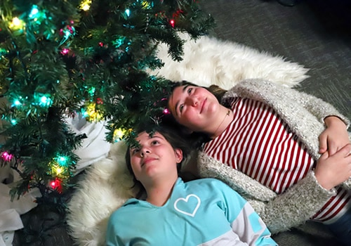 two girls laying underneath a Christmas tree
