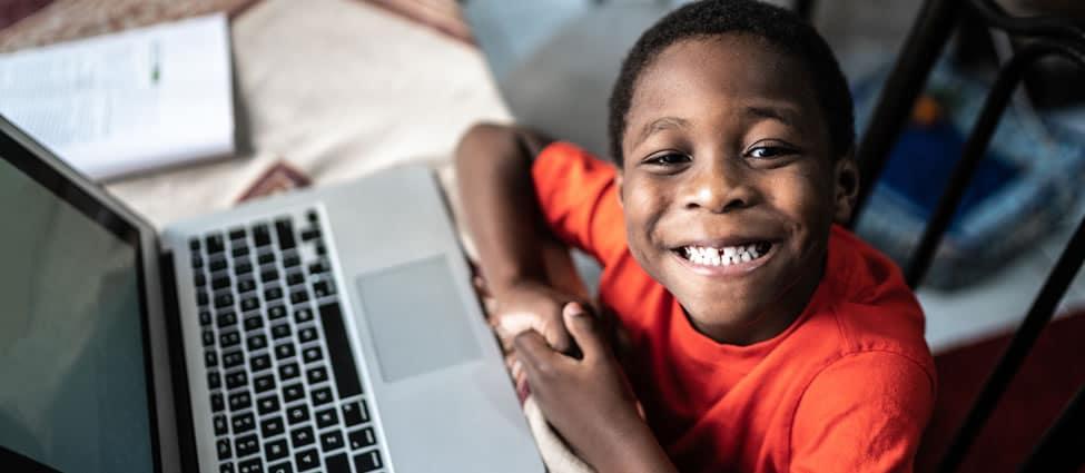 Boy doing school work on a laptop